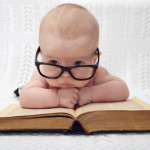 funny portrait of cute  baby in glasses lieing over an old big book (vintage style)